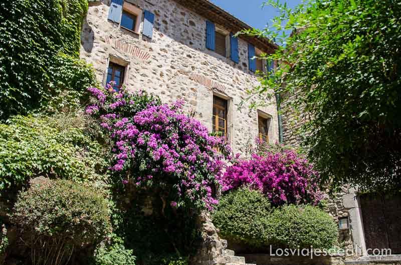 casa de piedra con macizos de flores en la puerta
