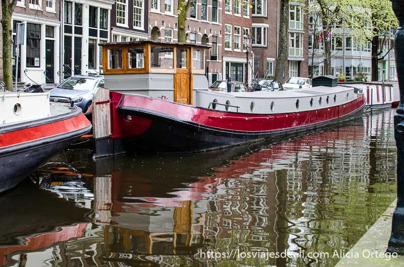 barco casa de color negro y rojo en un canal de amsterdam