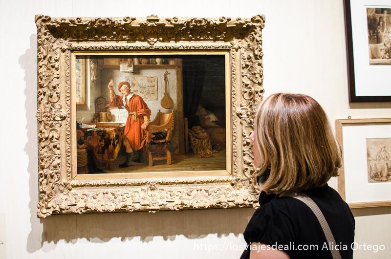 turista mirando un cuadro de la casa de rembrandt en amsterdam