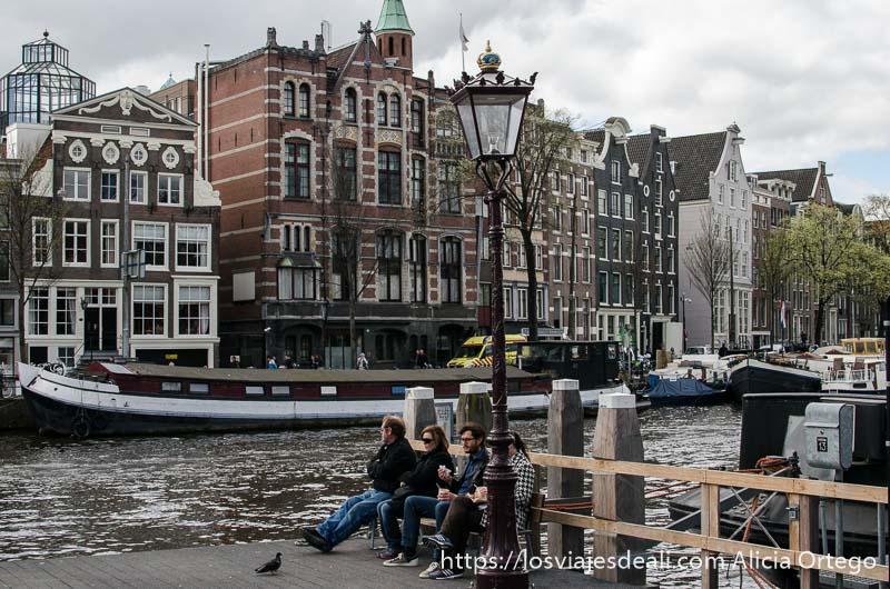 cuatro personas sentadas en un banco junto a un canal de amsterdam y detrás casas típicas