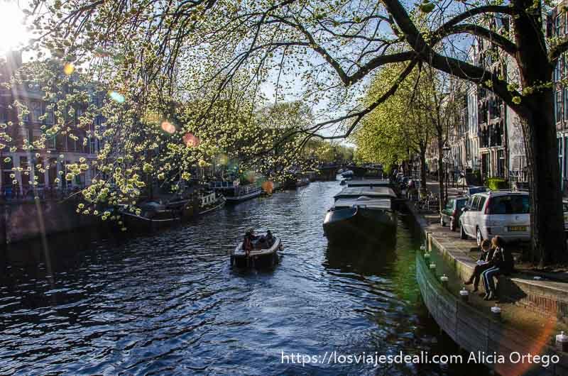 canal de amsterdam con dos chicas sentadas en el borde y una barca en el centro