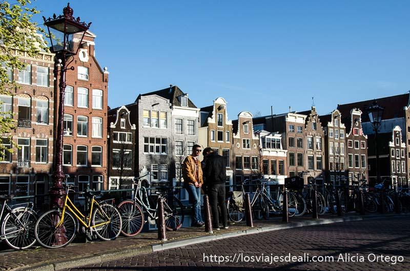 dos chicos apoyados en una hilera de bicicletas con casas típicas de amsterdam detrás