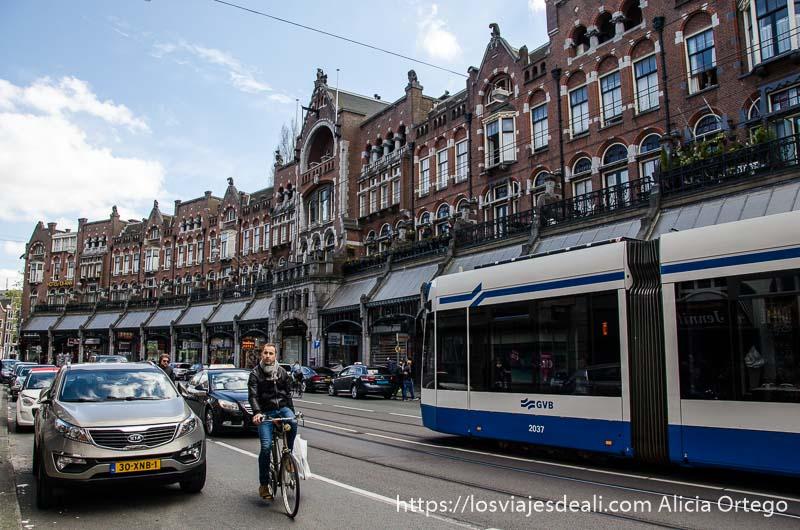 gran edificio antiguo que hace curva con tranvía y ciclista en primer plano