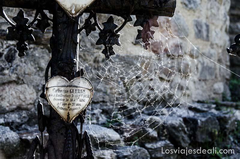 tumba antigua con cruz de hierro y una caja en forma de corazón con el nombre de la fallecida