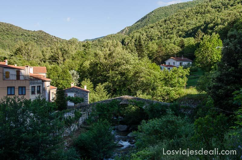 puente románico en un paisaje de montaña muy verde
