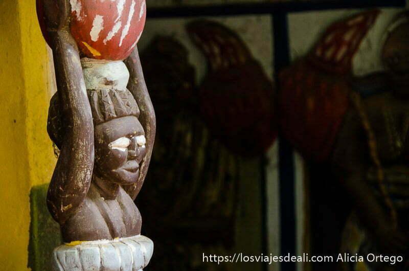 escultura de madera de mujer con jarro en la cabeza y ojos blancos