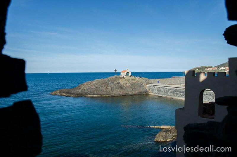 pequeña ermita en una península rodeada de mar vista a través de almenas de muralla