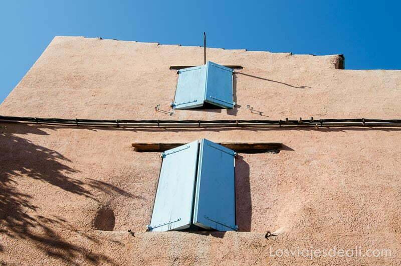 ventanas de madera azules en muro de color beige y cielo muy azul en collioure