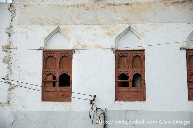 dos ventanas de madera con pequeños arcos al estilo árabe en una fachada blanca