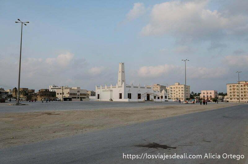 mezquita de estilo yemení pintada de blanco al fondo de una gran plaza