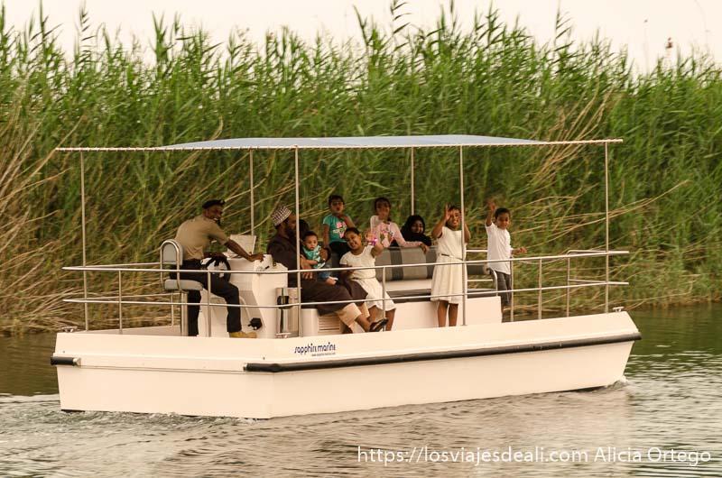 barca con familia omaní con muchos niños saludando a su paso