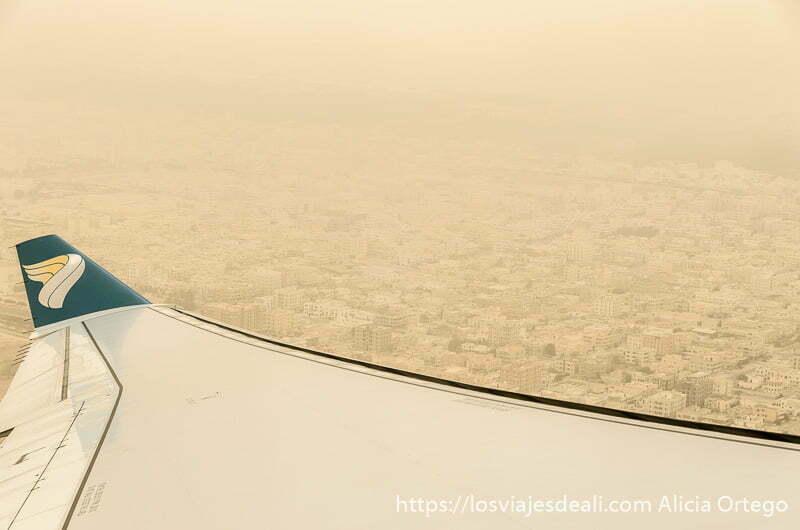 ala de avión con logotipo de oman air y debajo los edificios de salalah