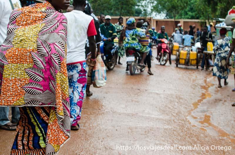 gente andando en un mercado africano con suelo de barro por la lluvia