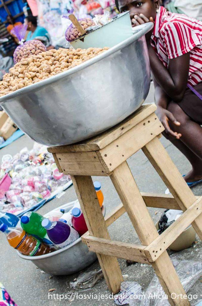 barreño lleno de chufas sobre banqueta de madera en un mercado de benin