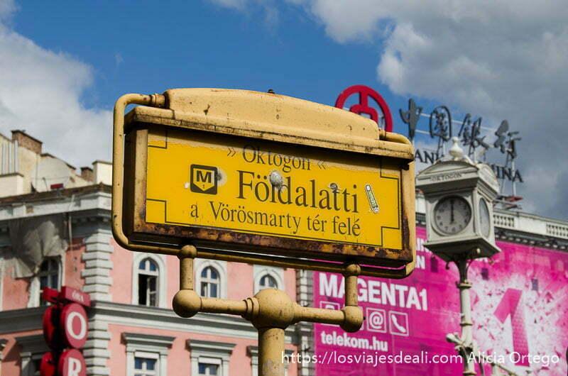 cartel de metro de color amarillo con edificios detrás cómo moverse por budapest