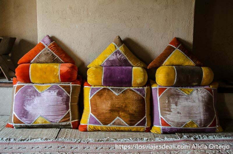 tres cojines de tercipelo de colores en el suelo sobre alfombra en fuerte de nizwa