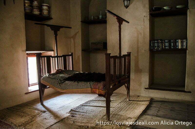 cama antigua de estructura de madera con colchón y telas de colores en el fuerte de nizwa