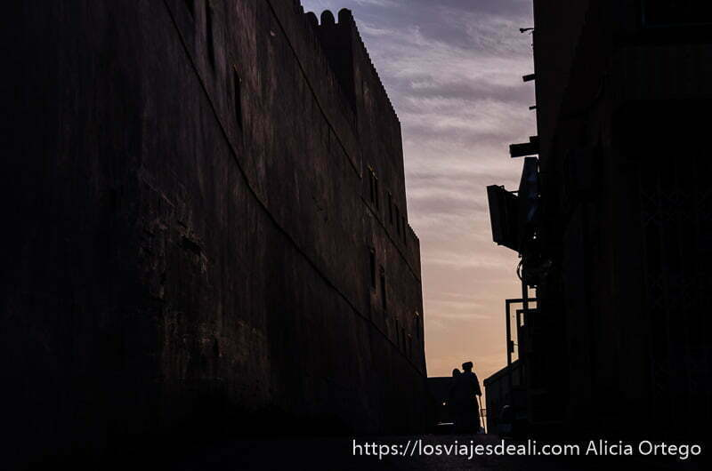 calle estrecha de nizwa al atardecer con silueta de hombre con turbante