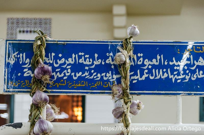 cartel azul con letras árabes y dos ristras de ajos colgando de él en el zoco de nizwa