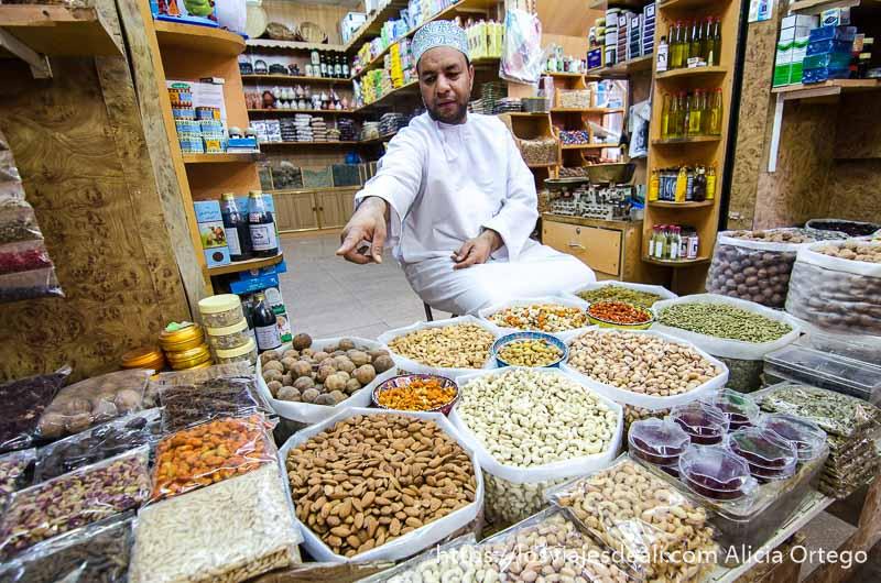 hombre señalando su oferta de frutos secos en el zoco de nizwa