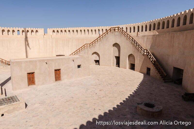 patio superior de la torre del fuerte de nizwa con escaleras para subir a las almenas