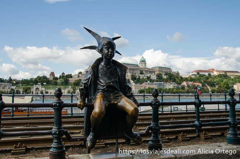 estatua famosa de budapest que es un niño sentado en barandilla de la calle con gorro de bufón calles de budapest