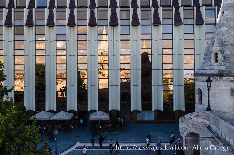 fachada de edificio moderno con cristales donde se reflejan las torres del bastión de los pescadores de budapest