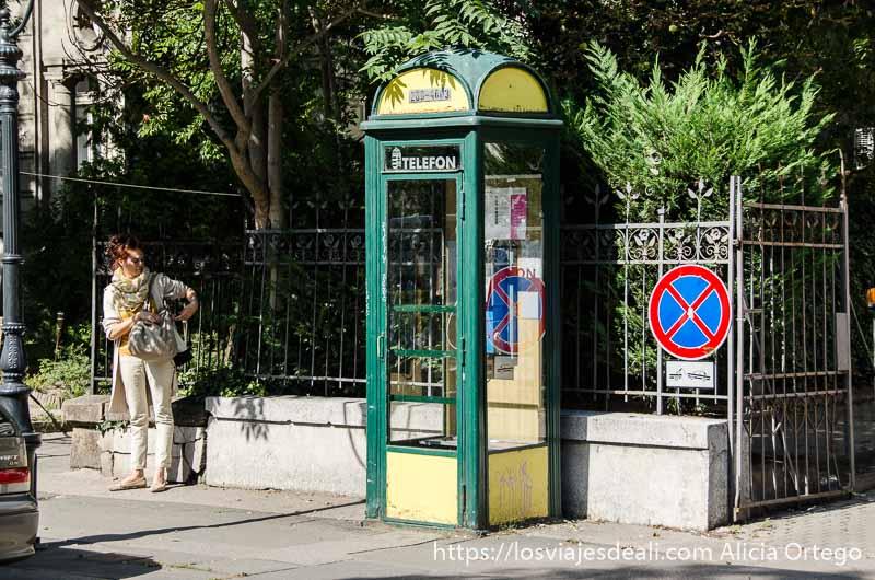 cabina telefónica pintada de verde y amarillo y chica joven al lado calles de budapest