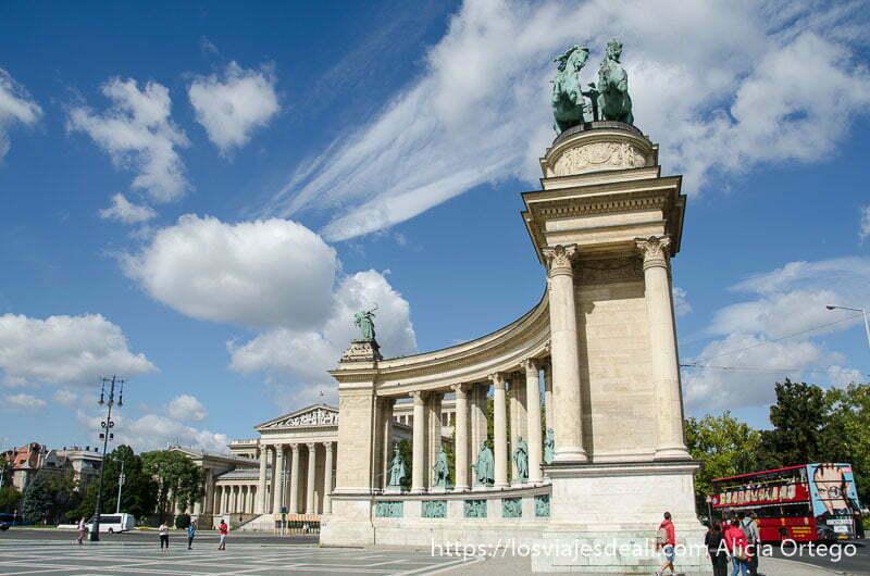 monumento con estatuas de bronce en la parte superior y nubes blancas en cielo azul calles de budapest