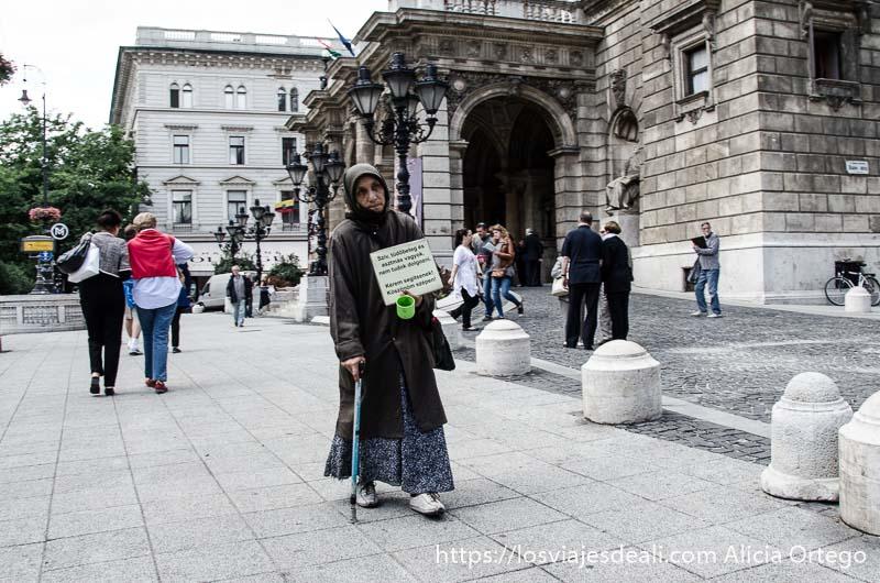 mendiga con bastón y cartel en la otra mano andando junto al edificio de la ópera calles de budapest