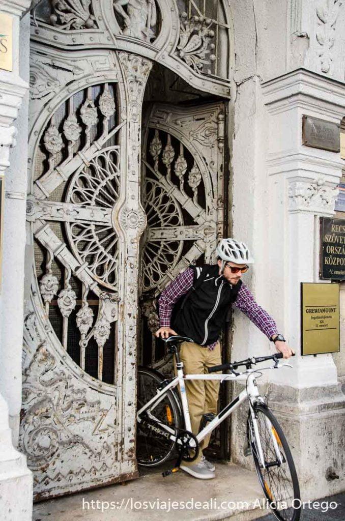 ciclista saliendo con su bici de portal de puerta de hierro con filigranas calles de budapest