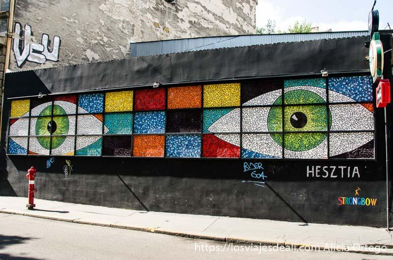 obra artística en un muro de la calle: dos ojos con pupilas verdes y cuadros de colores calles de budapest