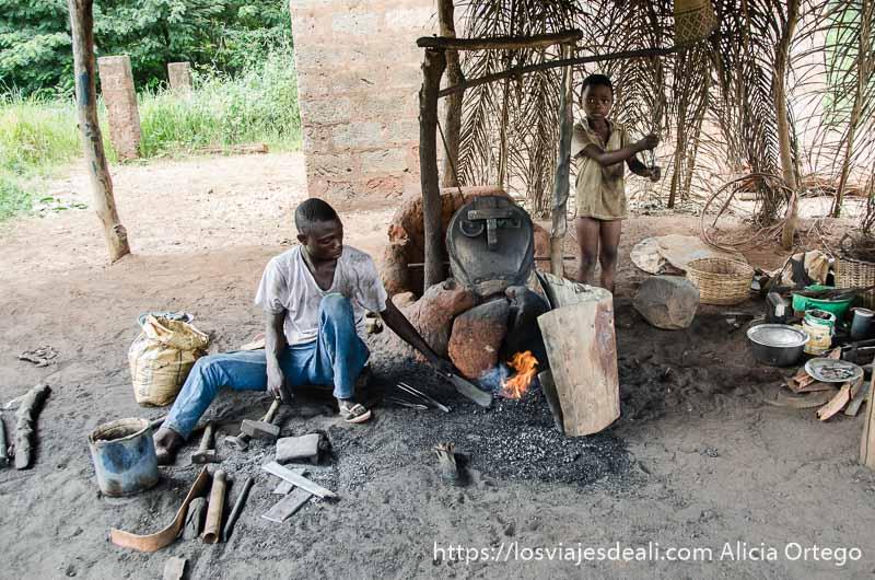herrero de abomey trabajando y su hijo pequeño accionando el fuelle hecho con piel de animal