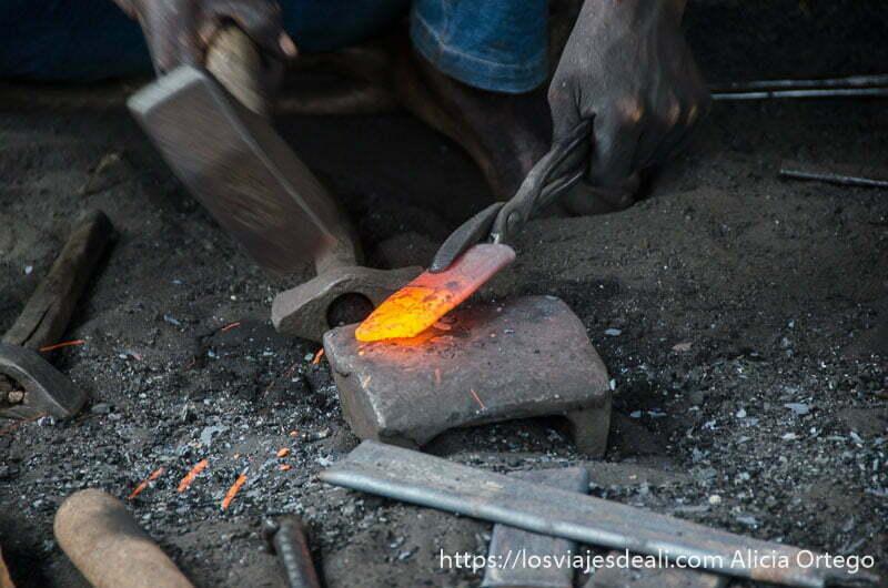 manos de herrero con martillo y un hierro candente sobre el yunque en abomey benin