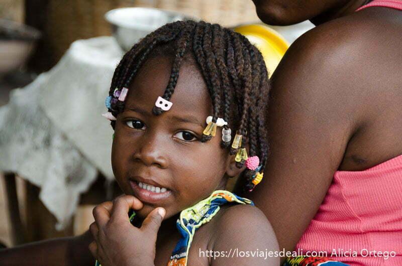 niña de abomey con peinado de trencitas y bolitas de colores en el final de cada una benin