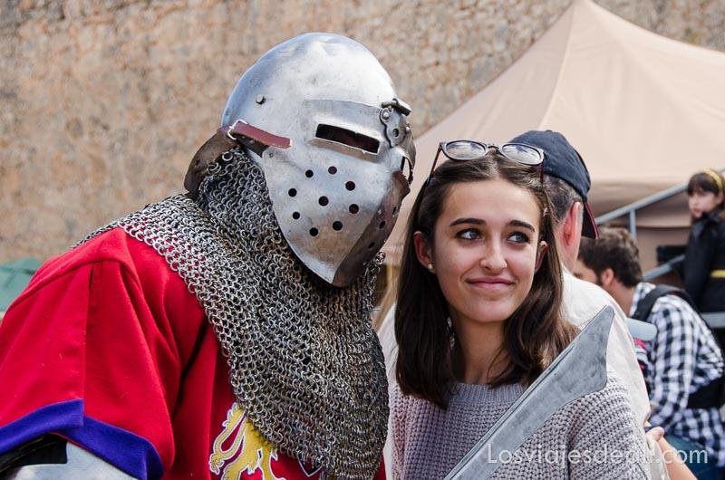 chica posando con guerrero que lleva casco de armadura puesto en el torneo internacional de combate medieval