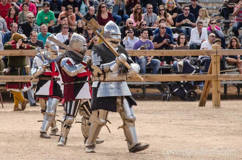 caballeros con armaduras andando en fila con las espadas al hombro en la arena torneo internacional de combate medieval