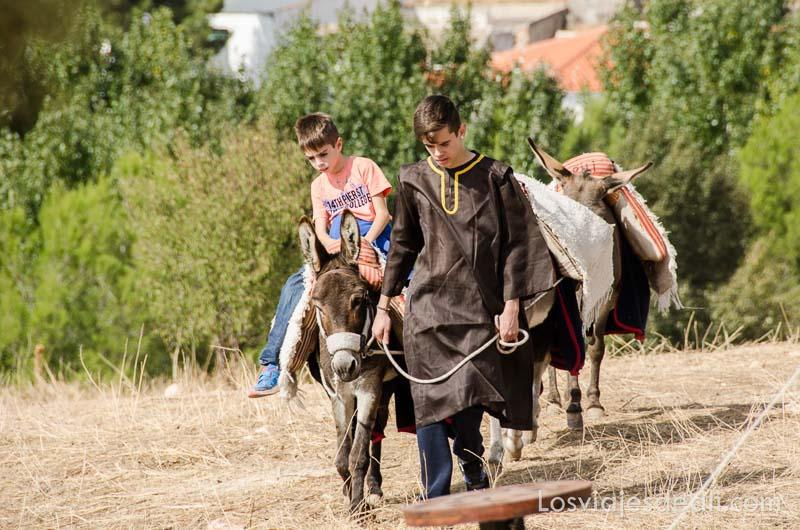 chico vestido de medieval llevando a un niño en un burrito torneo internacional de combate medieval