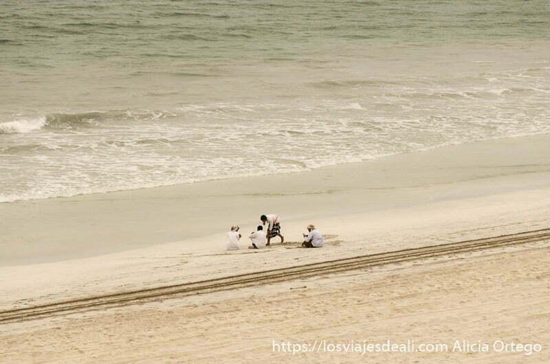 un grupo de hombres omaníes sentados en la playa junto al mar en salalah