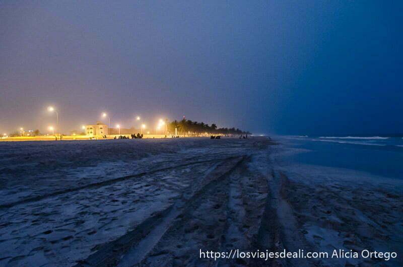 playa de salalah de noche con luces de chiringuitos y palmeras