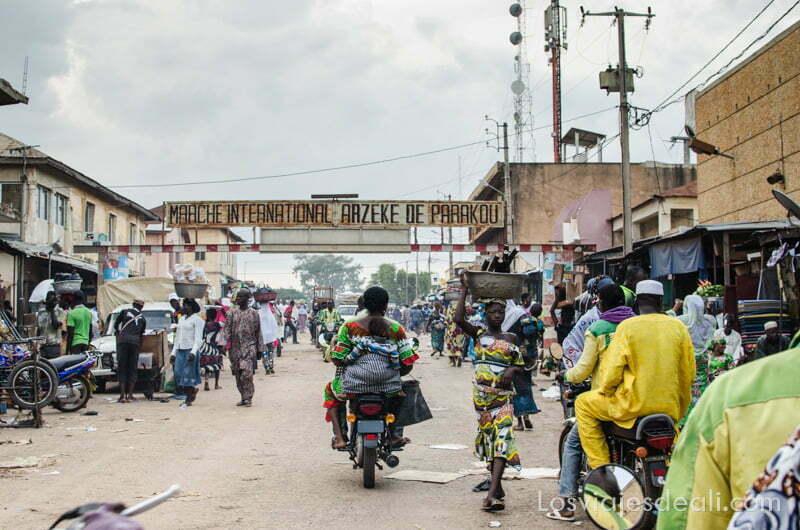calle principal con cartel del mercado de parojou y mujer en moto ruta en benin