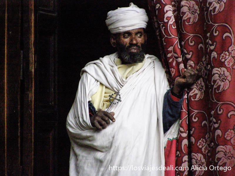 cura etíope envuelto en su shama blanca con una cruz en la mano iglesias de etiopía