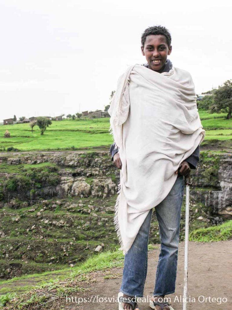 niño enfermo de polio que camina con bastón y sonríe a la cámara