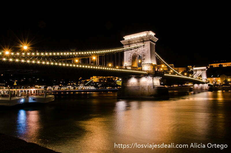 puente de las cadenas por la noche iluminado y reflejándose en el río puentes de budapest