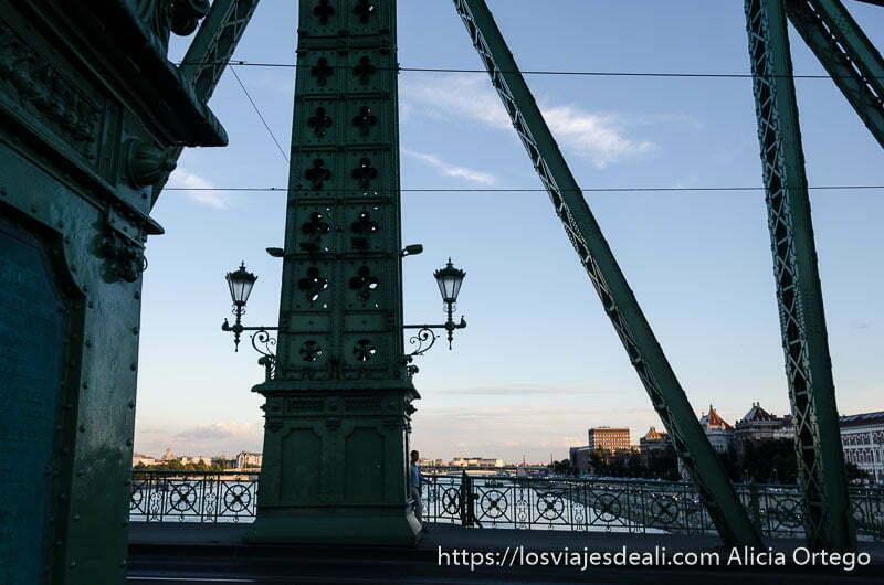 dos farolas apoyadas en la estructura de hierro de uno de los puentes de budapest