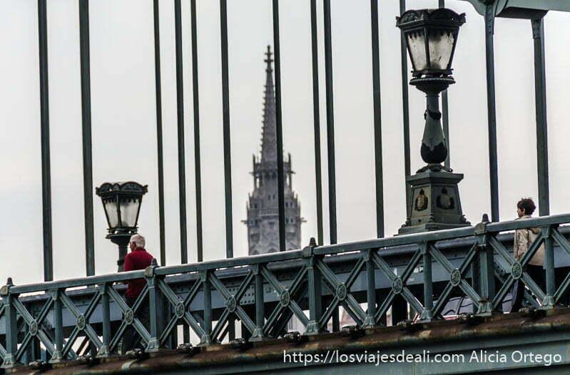 puente de las cadenas con un hombre de rojo pasando junto a la barandilla puentes de budapest