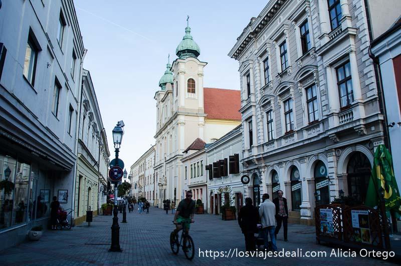calle con iglesia magiar con cúpulas de bronce en el campanario qué ver en pécs