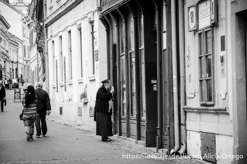 mujer mayor mirando escaparate de tienda antigua con helado en la mano qué ver en pécs