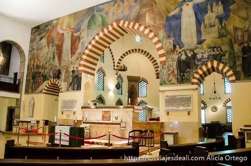 altar de iglesia bajo los arcos de la mezquita y pared llena de pinturas qué ver en pécs