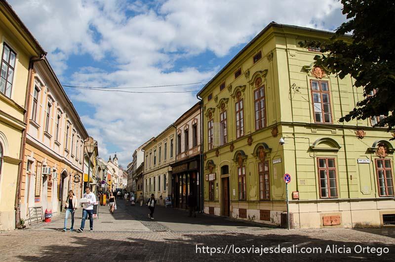 calle con edificios señoriales pintados de colores y cielo azul con nubes blancas qué ver en pécs